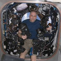 NASA Astronaut Don Pettit on board the ISS holding one of the cameras modified by Spencer's Camera & Photo.